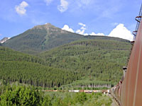 tall mountain with train going toward it