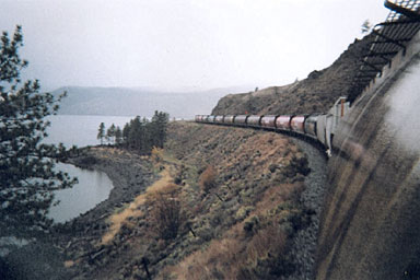 grain train and several cars travelling along beside water