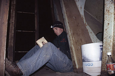 Reading by flashlight on the rear porch of a grain car